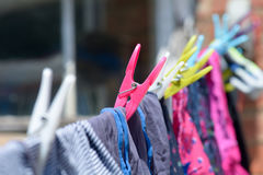 Clothes pegs and clothes on washing line Stock Photo