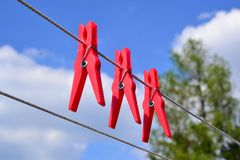 Clothes-pegs. On clothesline, red Stock Photo