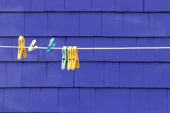 Clothes pegs detail on purple wall. Plastic pegs on a clothesline against purple shingled wall. Space for your text stock photos