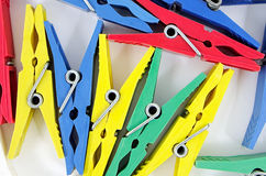 Clothes pegs. In a different color on a white background Royalty Free Stock Photo