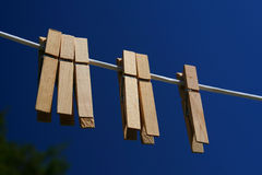 Clothes Pegs on a Line. Clothes Pegs on a washing line, shot against a blue sky Royalty Free Stock Images