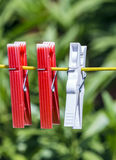 Clothes pegs on a line. Row of three clothes pegs hanging on a yellow line in a garden with blurred background Royalty Free Stock Photography