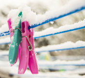 Clothes pegs on washing line under snow. Some snow on top of washing line royalty free stock image