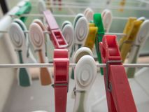 Clothes pegs on a white line dryer stock images