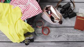 Clothes and purse with cosmetics. Binoculars near passport. Luggage and document for journey. Things on gray wooden floor stock video