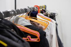Clothes rack with different clothes in the dressing room.  Royalty Free Stock Photo