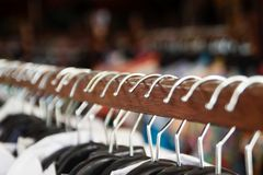 Clothes racks with hangers and with clothes on a blurred background. Clothes racks with hangers and with clothes on a blurred background inside shop royalty free stock photos