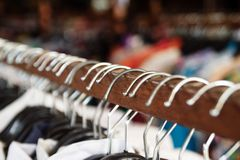 Clothes racks with hangers and with clothes on a blurred background inside shop. Wooden clothes racks with hangers and with clothes on a blurred background royalty free stock photos