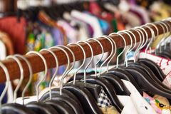 Clothes racks with hangers and with colorful clothes on a blurred background inside shop. Wooden clothes racks with hangers and with colorful clothes on a royalty free stock image