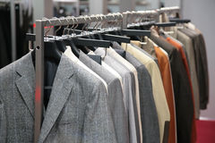 Clothes on racks in shop Stock Photography