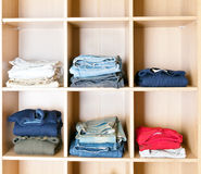 Clothes on regiments in a wardrobe Royalty Free Stock Image