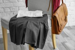 Clothes of schoolgirl on chair. Indoors Stock Photos