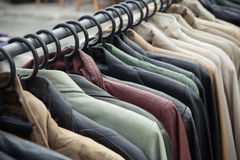 Clothes. Selective focus some used leather clothes hanging on a rack in a market, retro picture style royalty free stock photo