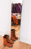 Clothes and shoes reflecting in the mirror. Leather boots and heap of clothing reflecting in the mirror Stock Photo