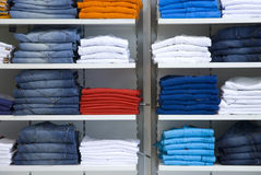 Clothes in the shop. T-shirts and jeans Stock Photos