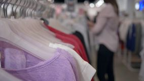 Clothes shop, fashionable new clothing hanging on hangers and shopper woman in unfocused background chooses purchases in