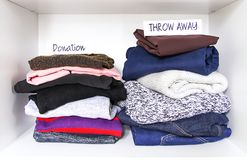 Clothes sorting in wardrobe on white shelf background. Donation, throw away paper notes. Clothes sorting in home wardrobe on white shelf background. Donation stock image
