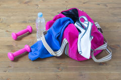 Clothes for sports with pink dumbbells. Pink dumbbells and a bag with things Royalty Free Stock Images