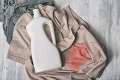 Clothes with stains and a bottle of detergent. Top view royalty free stock images