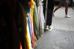 Clothes stall by the street. Clothes dresses stall near a street and people passing by Stock Photo