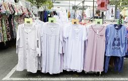 Clothes stand in a street market with a large sample of nightgowns royalty free stock photo