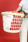 Clothes to the washing. Woman standing and holding in hands full laundry basket. Closeup on basket. Front view royalty free stock images