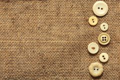 Clothes vintage buttons on burlap texture background with copyspace Stock Photography