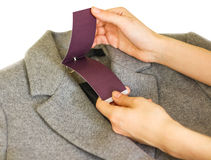 Clothes, wear and fashion concept - close up of hand holding pri. Ce tag of grey wool coat Stock Photos