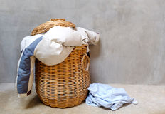Clothes in wicker basket. Overflowing wicker laundry basket. Household chore concept stock images