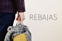 Clothes and word rebajas, sale in spanish. Closeup of a young caucasian man seen from behind carrying a paper shopping bag full of clothes and the word  rebajas Royalty Free Stock Image