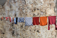 Clothesline. Colorful clothes drying by an old wall royalty free stock image