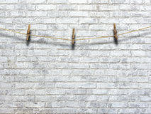 Clothesline with clothespins on a background of a brick wall Royalty Free Stock Image
