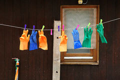 Clothesline with colored gloves fixed with colored pegs. A clothesline full of colorful rubber gloves, hung on colored pegs Royalty Free Stock Images