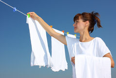 Clothesline, laundry, drying. A woman collecting clothes from a clothesline isolated on a blue sky background Stock Photo