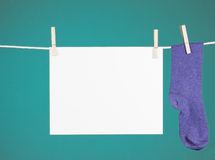 Clothesline Memo. A blank paper sign hanging from a clothesline next to a purple sock on a turquoise background royalty free stock photo