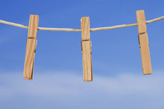 Clothesline and pegs on blue sky background Royalty Free Stock Photos