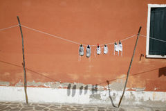 Clothesline with shoes. Clothesline with shoes in front of colorful house on the island of Burano in the Venetian lagoon - Italy Stock Photo