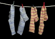 Clothesline and sox. Clothesline with some multicolored sox fixed with clothes pins in black back Stock Photo