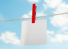 Clothespin. Blanc white paper sheet fixed on a cord a red clothespin on a background of the blue sky with clouds Royalty Free Stock Image