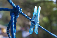 Clothespin on a clothes line. Close-up of a blue wet clothspin hanging on a blue wire in the sunlight. Water drops hanging on the clothspin Royalty Free Stock Images