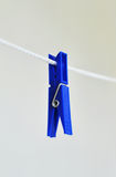 Clothespin on clothesline. Blue clothespin on white clothesline Stock Image