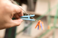 Clothespin in a hand on a clothesline.  Stock Photo