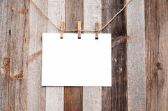 Clothespin hanging with blank paper on wooden background Stock Image