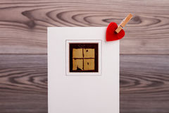 Clothespin and heart on card. Stock Photo