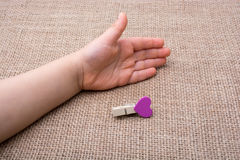 Clothespin with a heart shaped object in hand Royalty Free Stock Photos