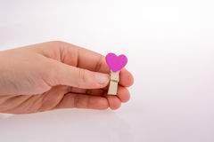 Clothespin with a heartshape in hand Royalty Free Stock Image