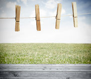 Clothespin on a laundry line outside above wooden boards. With sky on the background Royalty Free Stock Images