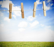 Clothespin on a laundry line outside with bright blue sky. With green landscape Royalty Free Stock Image