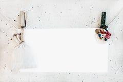 Clothespines del muñeco de nieve de la Navidad que sostienen la tarjeta de papel y el saco Fotos de archivo