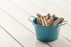 Clothespins in a bucket. Some clothespins in a bucket on a white wooden table royalty free stock image